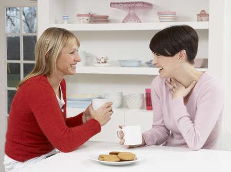 two people talking: Dos mujeres disfrutando caliente bebida en cocina