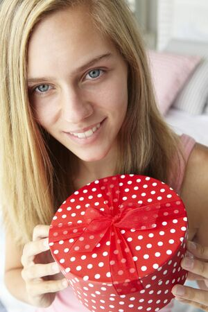 and guessing: Teenage girl holding gift box