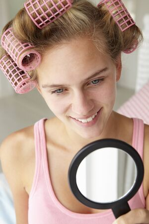 Teenage girl with hair in curlers photo