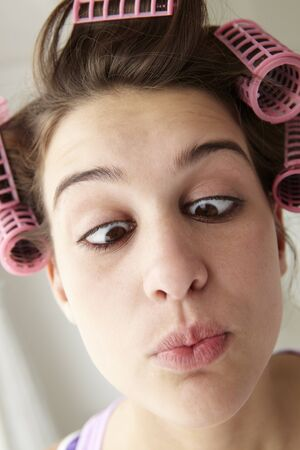 Teenage girl with hair in curlers pulling a face photo