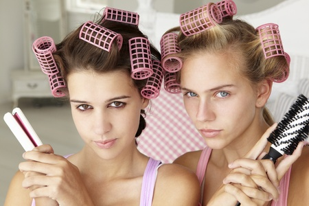 curling: Teenage girls with hair in curlers Stock Photo