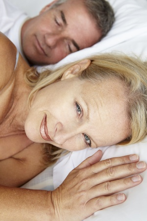 Mid age couple in bed woman awake photo