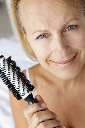 Mid age woman holding hairbrush photo