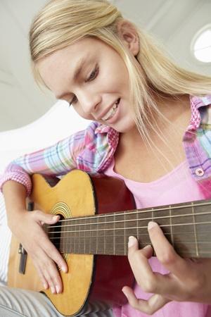 Teenage girl playing acoustic guitar photo