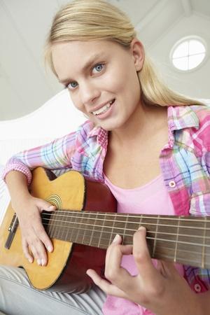 seventeen: Teenage girl playing acoustic guitar Stock Photo