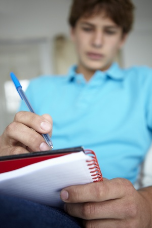 Teenage boy writing in notebook photo