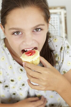 10 year old: Young girl eating cupcake