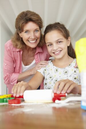 Young girl baking with grandmother photo