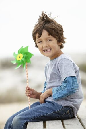 Young boy holding windmill into the wind photo