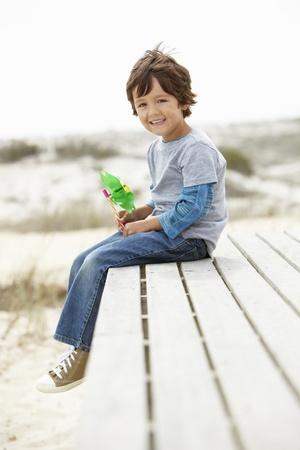 turns of the year: Chico joven en la playa con molino de viento