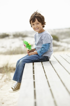 Young boy on beach with windmill photo
