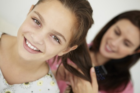 Mother brushing daughters hair photo
