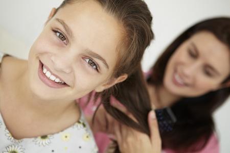 Mother brushing daughters hair Stock Photo