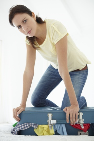 packing suitcase: Woman struggling to close suitcase
