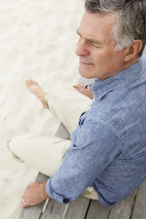 greying: Senior man sitting by beach