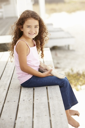 little girl sitting: Little girl outdoors holding starfish