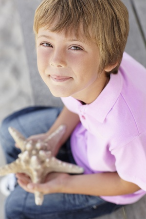 Young boy outdoors holding starfish photo