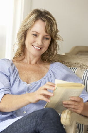 mid age: Mid age woman reading a book Stock Photo