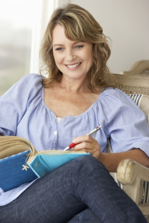Mid age woman writing in notebook Stock Photo - 11190871
