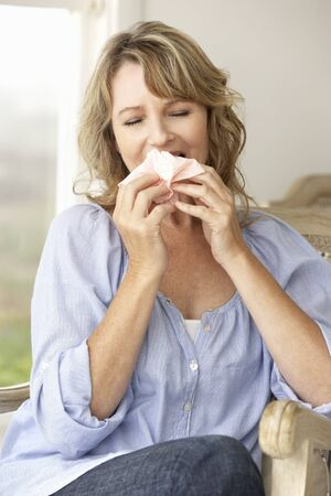 sneeze: Mid age woman sneezing Stock Photo