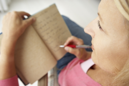 journals: Senior woman writing in notebook Stock Photo