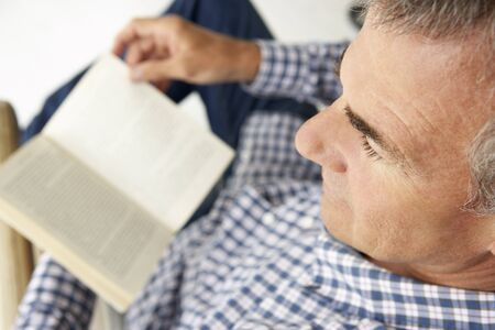 greying: Mid age man reading a book Stock Photo