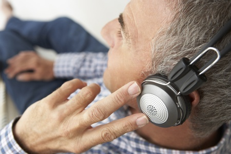 greying: Mid age man wearing headphones