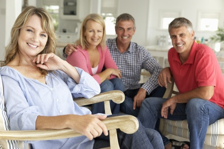 attractive couch: Mid age couples relaxing at home