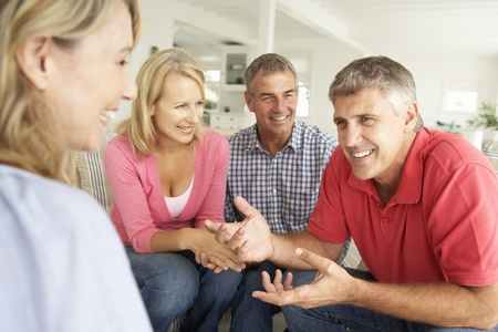 greying: Mid age couples chatting at home