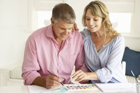 greying: Mid age couple painting with watercolors Stock Photo