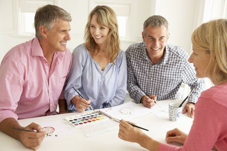 greying: Mid age couples painting with watercolors Stock Photo