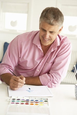 Mid age man painting with watercolors Stock Photo