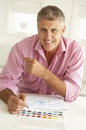middle aged man: Mid age man painting with watercolors Stock Photo