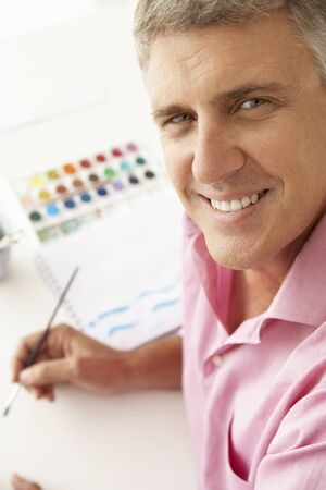 greying: Mid age man painting with watercolors Stock Photo