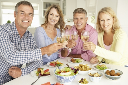 greying: Mid age couples enjoying meal at home Stock Photo
