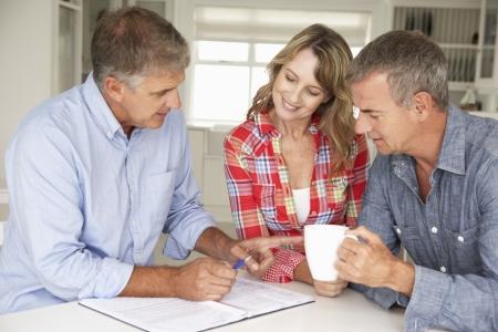 Medio leeftijd paar met financiële adviseur thuis