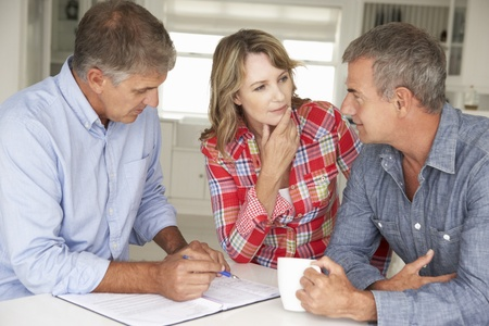 Mid age couple with financial advisor at home Stock Photo - 11190693