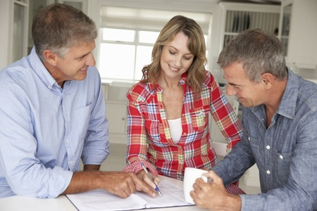 Mid age couple with financial advisor at home photo