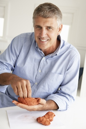 Mid age man clay modelling Stock Photo - 11190367