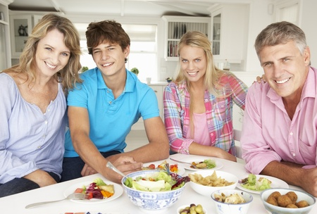 mid teens: Family enjoying meal at home