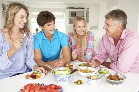 disfrutar: Familia disfrutando de comida en su casa