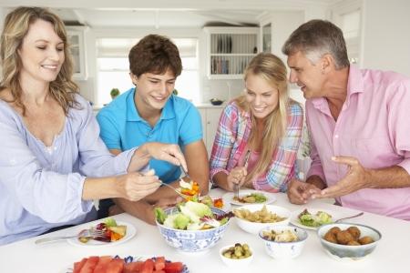 padres hablando con hijos: Familia disfrutando de comida en su casa