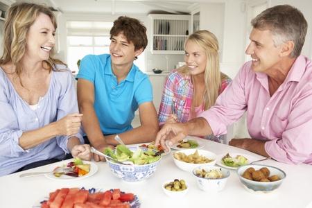 pareja adolescente: Familia disfrutando de comida en su casa