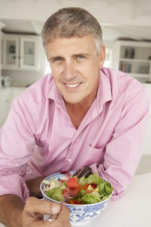 male age 40's: Mid age man eating salad