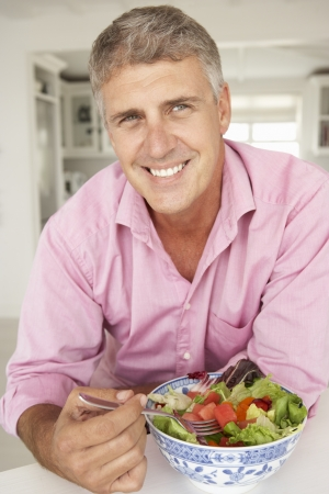 middle aged men: Mid age man eating salad