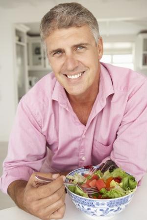 Mid mężczyzna wiek jeść sałatki