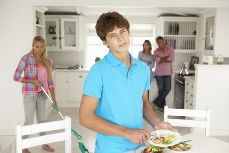 reluctant: Teenagers not enjoying housework Stock Photo