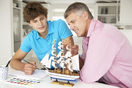 Father and teenage son model making and painting Stock Photo