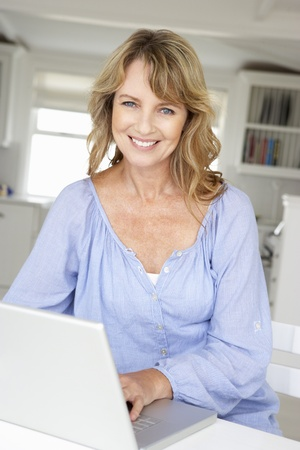 using the laptop: Mid age woman using laptop Stock Photo