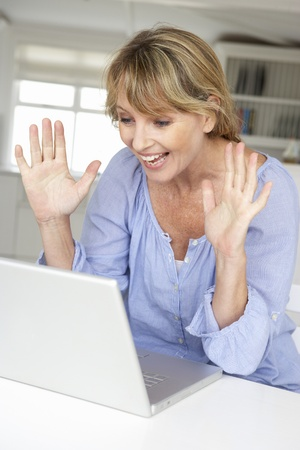 Mid age woman using laptop photo
